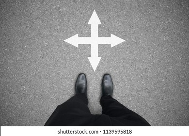 Businessman in black leather shoes standing at the four ways crossroad making decision which way to go - two ways to choose.