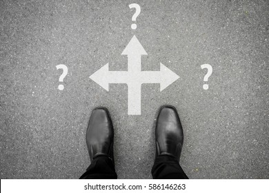 Businessman in black shoes making decision at the crossroad which way to go - three ways to choose but all are uncertain future.