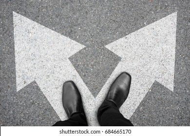 Businessman in black shoes standing at the crossroad making decision which way to go. Decision making concept.