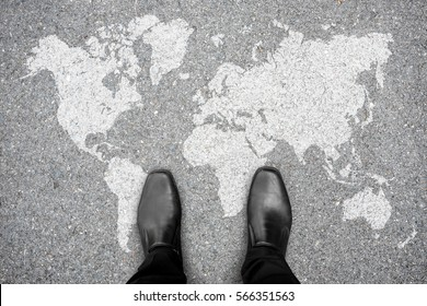 Businessman in black shoes standing on world map representing global business and business trip.