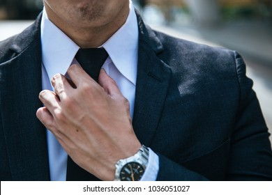 Businessman in black suit and adjusting his necktie.