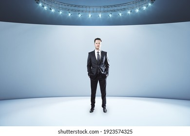 Businessman in black suit in the center of empty light room with led lights on top