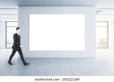 Businessman in black suit goes by blank white poster on the wall in the center of empty spacious hall with city view