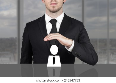 businessman in black suit holding protective hand above employee