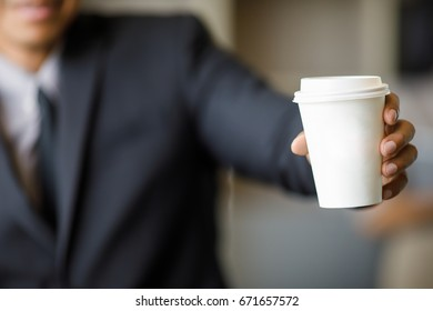 Businessman in black suit holding white paper coffee cup