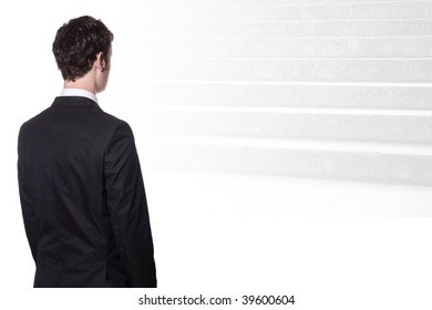 businessman in a black suit looking at stairs