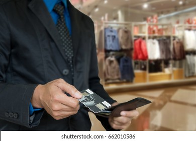 Businessman in black suit picking credit card in wallet on blur background of shop at mall.