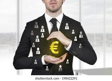 businessman in black suit protecting golden euro symbol with hands people