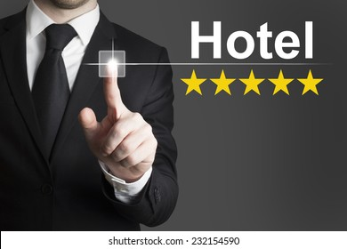 businessman in black suit pushing button hotel golden star rating