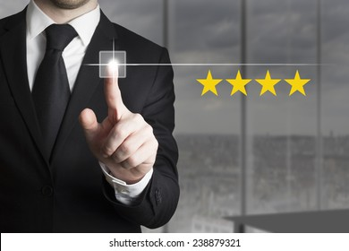 businessman in black suit pushing button four stars
