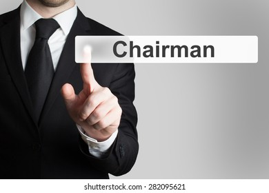 businessman in black suit pushing button chairman