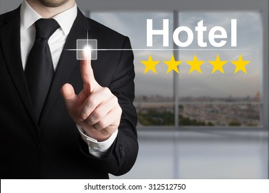 businessman in black suit pushing touchscreen button hotel five star rating