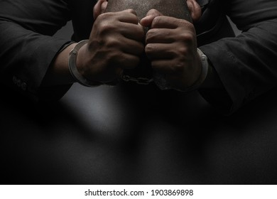A businessman in a black suit puts handcuffs on the table and the black table. Corruption, bribery, illegal transactions