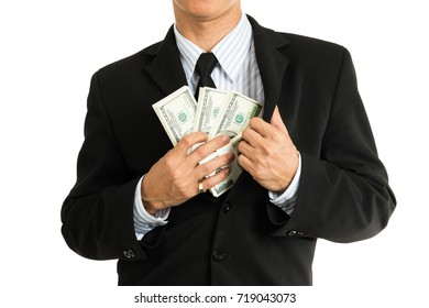 A businessman in a black suit putting money in his pocket. Photo isolated on white background.