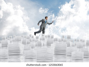 Businessman in black suit running with phone in hand on pile of documents with cloudly skyscape on background. Mixed media.