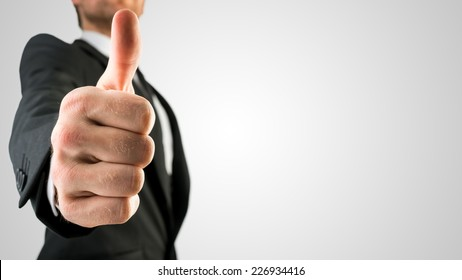 Businessman in Black Suit Showing Thumbs Up Sign, Emphasizing Approval or Satisfaction, in Close Up. Isolated on Gray Background.