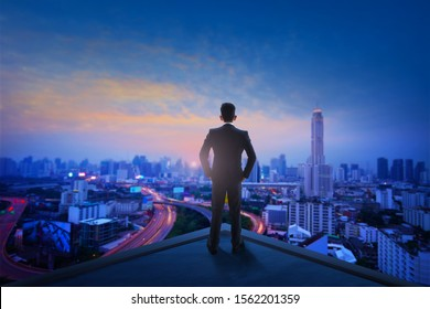 Businessman with black suit standing on top of building of city during sunrise early morning