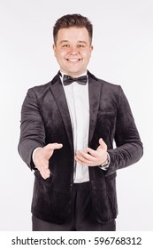 businessman in black suit stretching out his hand for shaking while. emotions, facial expressions, feelings, body language, signs. image on a white studio background.