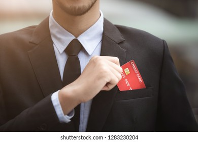 businessman in black suit take his credit card from his suit pocket