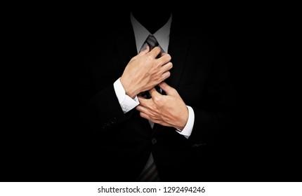 Businessman in black suit tying necktie, on black background