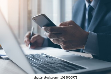 Businessman in black suit using mobile smart phone and working on laptop computer, browsing internet and writing on paper notebook in modern office. Man working on electronics devices with copy space