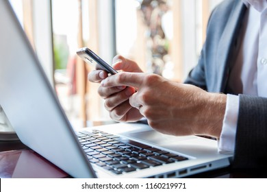 Businessman in black suit using mobile smart phone and working on laptop computer, browsing internet in modern office. Man working on electronics devices with copy space