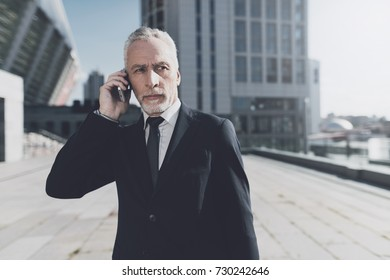 Businessman in black suit waiting for telephone answer. Serious look demonstrates serious intentions.