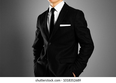 Businessman in a black suit, white shirt and tie. Studio shooting.