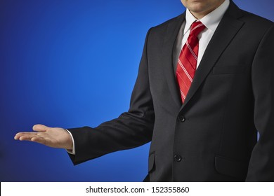 Businessman in a black suit, white shirt and red tie on a blue background shows an empty hand