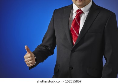 Businessman in a black suit, white shirt and red tie on a blue background shows the hand symbol of success