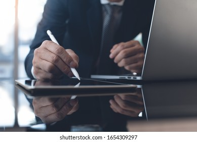 Businessman in black suit working in modern office. Business man with stylus pen signing on digital tablet screen, reviewing business report with laptop computer on glass table, close up