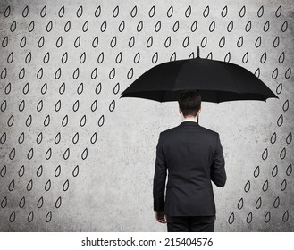 Businessman with black umbrella standing under drawing storm. Photo over concrete background