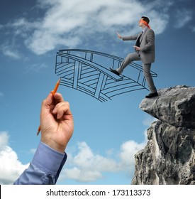 Businessman in a blindfold stepping off a cliff ledge with giant hand drawing a bridge for a safe crossing concept for building bridges, risk, challenge, conquering adversity, ignorance and assistance