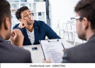businessman blowing bubble gum during job interview, business concept
