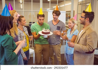 Businessman blowing candles on her birthday cake in the office