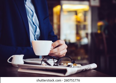 Businessman in a blue jacket with a cup of coffee, reading glasses, newspaper and smartphone in a cafe at the table, close-up