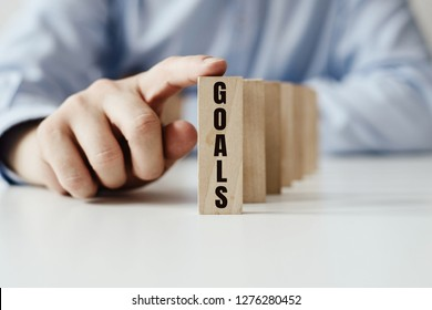 Businessman in a blue shirt arranges wooden jigsaw blocks with the words with plans to implement and the main or pursuing goals. New Year's resolutions, making dreams come true, promises.