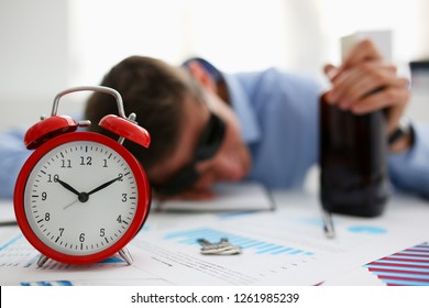 Businessman in blue shirt asleep at work on the background of a bottle of alcohol, overslept because stormy night party with a drink after corporate on January 1 celebrated new year very bad hangover