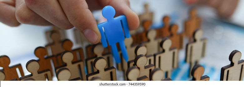 A businessman in blue shirt is holding a magnifying glass in his hand, is searching for personnel or people. Detective looking for missing person crowd of miniature figures choosing most suitable one