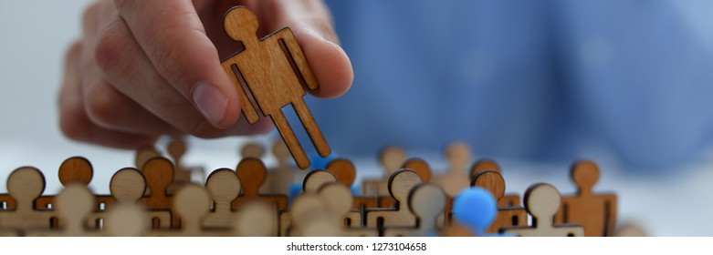 Businessman in blue shirt is holding people figure his hand, is searching for personnel or people. Detective looking for missing person crowd of miniature figures choosing most suitable one