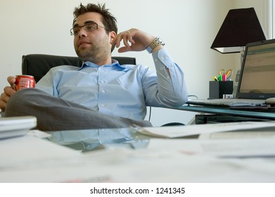 A businessman in a blue shirt sitting at his cluttered desk and looking away.