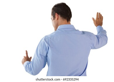 Businessman in blue shirt touching interface against white background