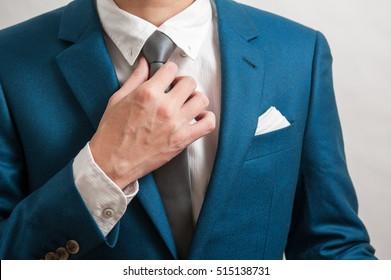 businessman in blue suit adjusting tie