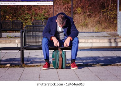 businessman in blue suit waiting at train station looking exhausted