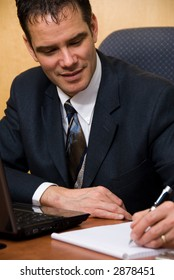 Businessman in a board room with his grey laptop