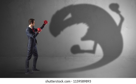 Businessman with boxing glove fighting with a big monster shadow