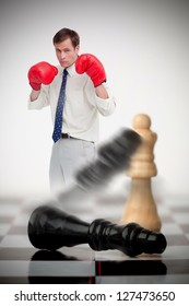 Businessman in boxing gloves knocking over chess pieces on a chessboard