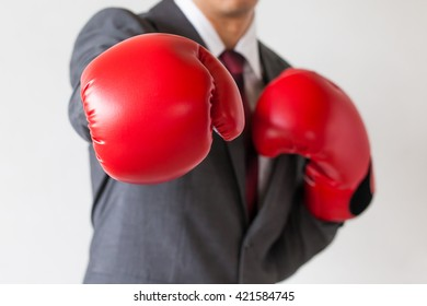 Businessman in boxing gloves launching a punch isolated on white background