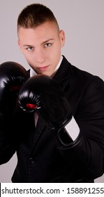 Businessman in boxing gloves on gradient background.