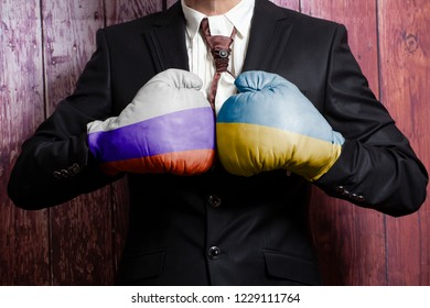 Businessman in boxing gloves with Russian and Ukraine flag. Russia versus Ukraine concept.